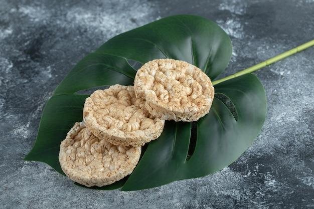 Drie gepofte rijstwafels op groen blad