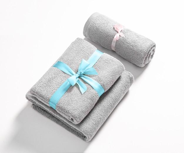Drie gerolde en gevouwen badstofhanddoeken die door roze en blauw geïsoleerd lint worden gebonden. stapel grijze badstofhanddoeken tegen een witte achtergrond.