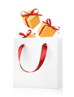 Drie geschenkdozen die in een witte geschenkzak vallen die op een witte achtergrond wordt geïsoleerd