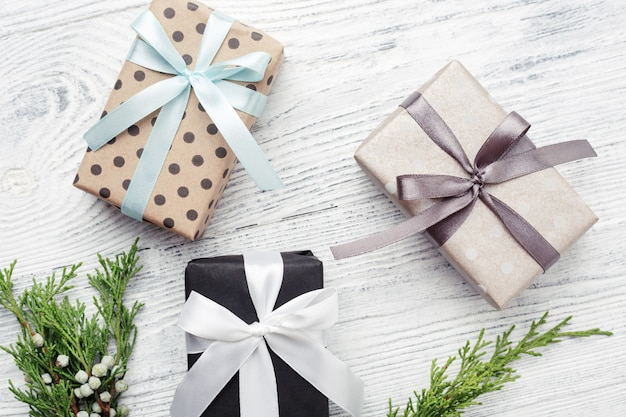 Drie geschenkdozen en groene twijgen op witte houten achtergrond tweede kerstdag.