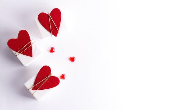 Drie geschenkdozen in wit papier en met hartjes liggen op een witte achtergrond.