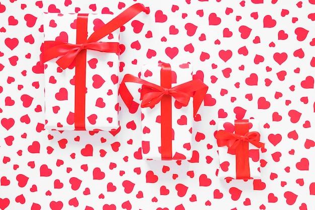 Drie geschenkdozen met rode linten op tafel