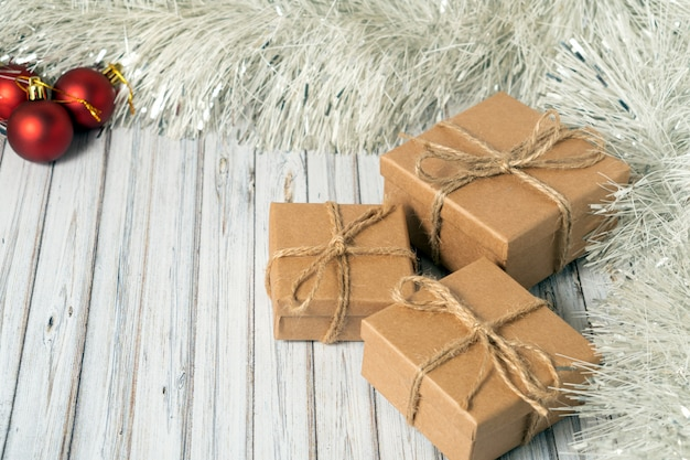 Drie geschenkdozen op een houten tafel versierd met een slinger en rode kerstballen voor het nieuwe jaar of xmas. post, koerier of bezorgservice concept. kopieer ruimte