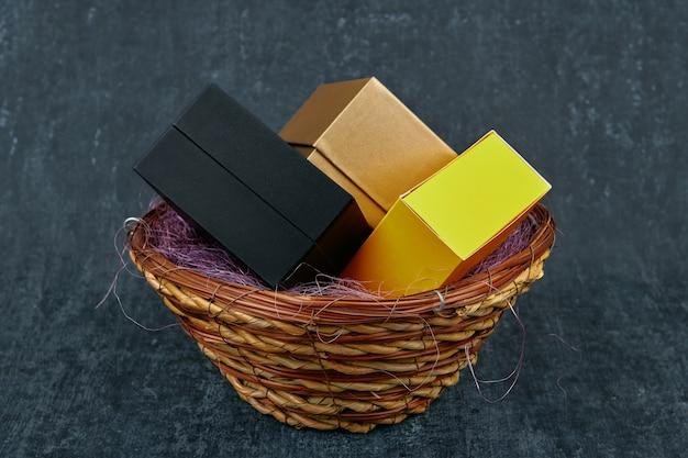 Drie geschenkdozen van verschillende kleuren in een rieten mand