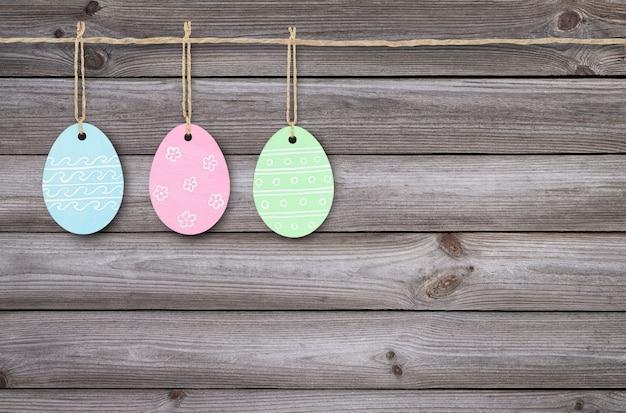 Drie geschilderde houten paaseieren die op een houten achtergrond hangen