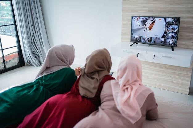 Drie gesluierde vrouw liggend op het bed genieten van het kijken naar de tv