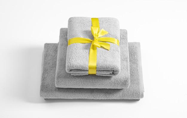 Drie gevouwen badstofhanddoeken die door geel geïsoleerd lint worden gebonden. stapel grijze badstofhanddoeken tegen een witte achtergrond.