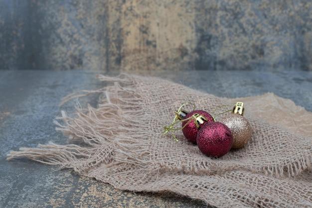 Drie glanzende kerstballen op jute.