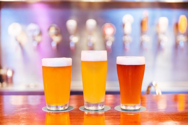 Drie glazen ambachtelijk bier met schuim en verschillende kleuren van licht tot donker