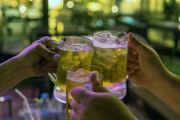 Drie glazen bier proosten samen tussen vrienden in de bar en het restaurant met weinig licht