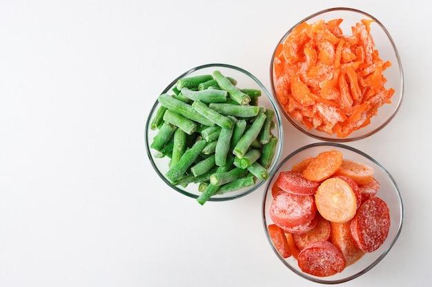 Drie glazen containers met bevroren groenten op een lichte achtergrond