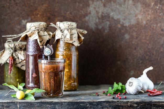 Drie glazen flessen geassorteerde georgische tkemali-saus met ingrediënten op rustieke houten tafel. kopieer ruimte