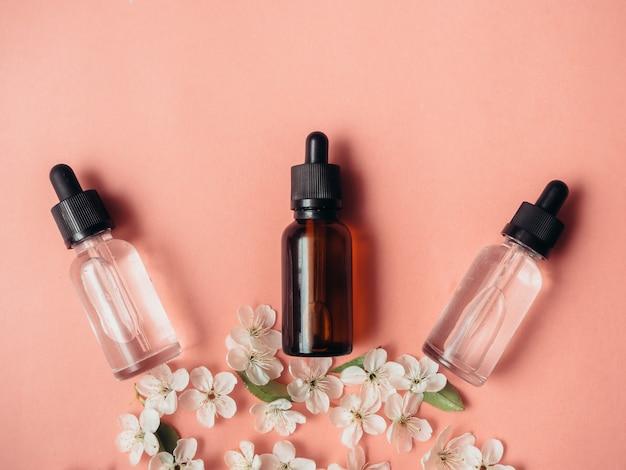 Drie glazen flessen met olie, parfum op een roze oppervlak met bloeiende kersen. platliggend, minimalisme.