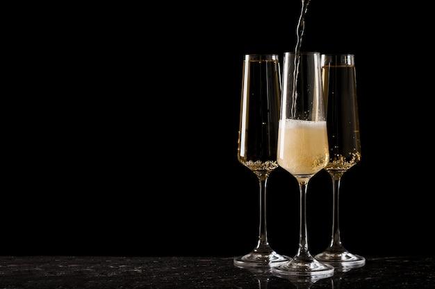 Drie glazen gevuld met mousserende wijn op een zwarte ondergrond