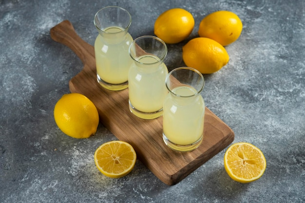 Drie glazen kannen koude limonade op een houten bord