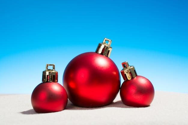 Drie glazen kerstballen op het strand