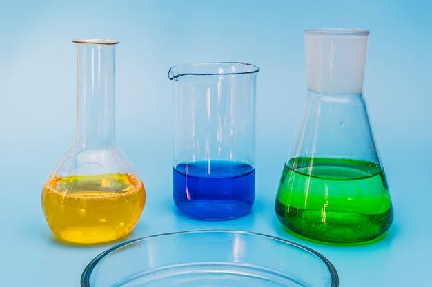 Drie glazen laboratoriumkolven met oplossingen van geel, groen en blauw op een zachte blauwe medische achtergrond. het concept van medische en chemische experimenten en onderzoek. detailopname. ruimte kopiëren.