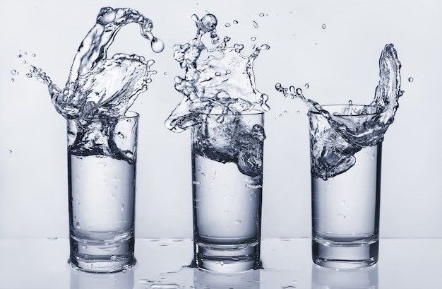 Drie glazen met opspattend water. spetterend water. water eruit.