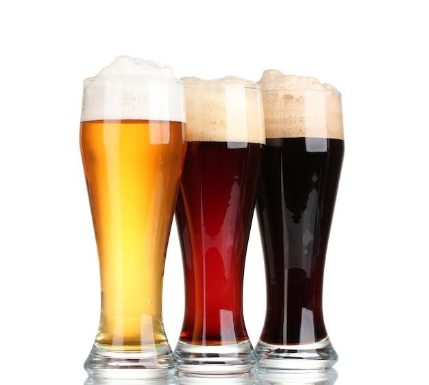 Drie glazen met verschillende bieren op wit wordt geïsoleerd