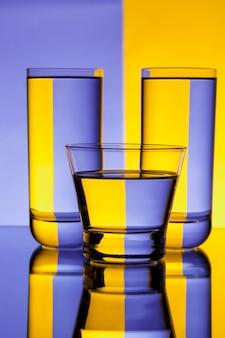 Drie glazen met water over paarse en gele muur