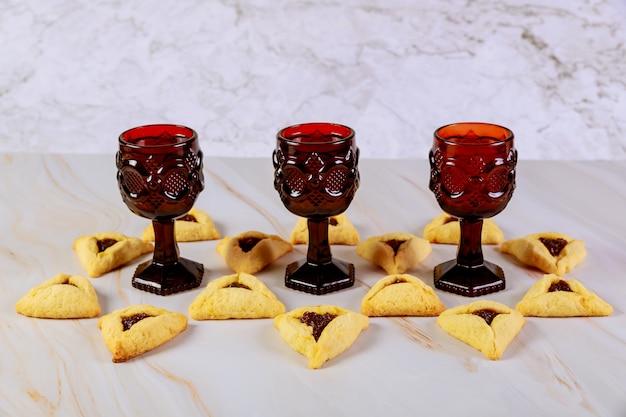 Drie glazen met wijn en hamantaschen koekjes.