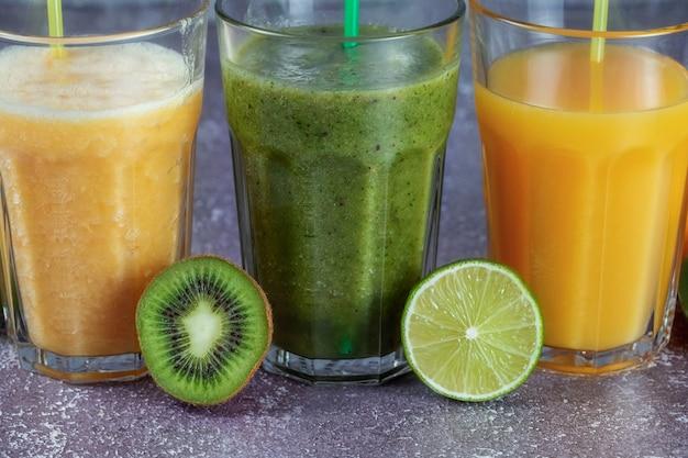 Drie glazen op een rij met jus d'orange en banaan oranje kiwi en spinazie smoothie omgeven door helften fruit op een grijze betonnen achtergrond. het concept van afvallen en goede voeding.
