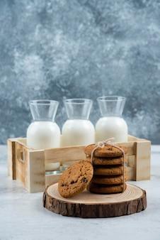 Drie glazen pot melk en stapel koekjes op marmeren tafel.