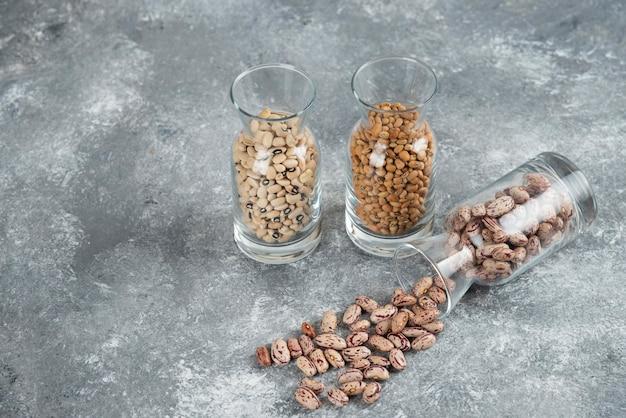 Drie glazen pot met onvoorbereide bonen op een grijze tafel.