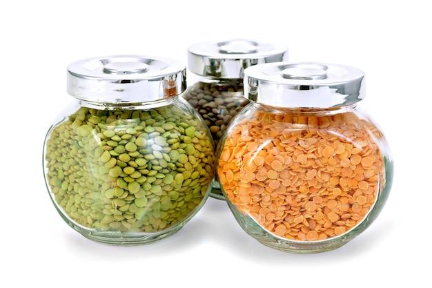 Drie glazen potten met groene, rode, bruine geïsoleerde linzen