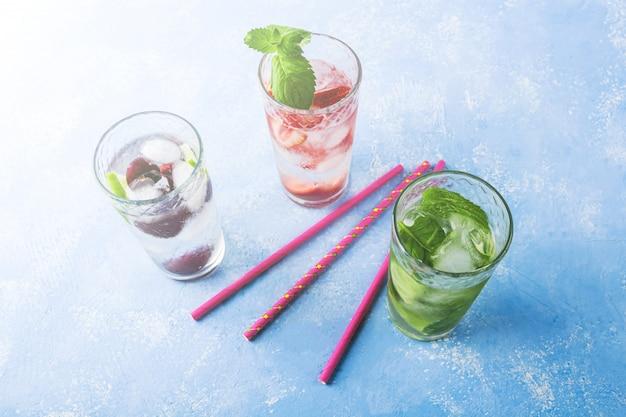 Drie glazen verfrissend koel detox drankje met aardbei, limoen, kers en munt. diverse zomerlimonades of ijsthee. mojito cocktails met ijsblokjes.