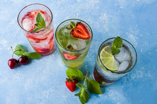 Drie glazen verfrissende koele detox-drank met aardbei, limoen, kers en munt