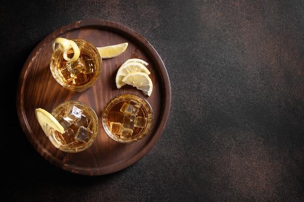 Drie glazen whisky geserveerd op rotsen met citroen op bruine achtergrond. kopieer ruimte.