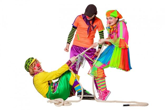 Drie glimlachende clowns met kabel die op de witte achtergrond wordt geïsoleerd