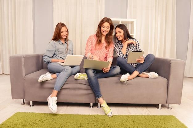 Drie glimlachende mooie meisjes die op de bank zitten en aan laptop werken