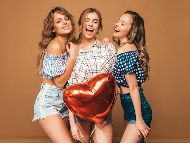 Drie glimlachende mooie sexy vrouwen in de kleren van de geruite overhemdszomer. meisjes poseren. modellen met hartvormige ballon. klaar voor valentijnsdag van de viering