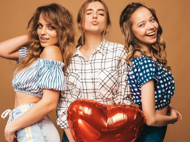 Drie glimlachende mooie vrouwen in de kleren van de geruite overhemdszomer. meisjes poseren. modellen met hartvormige ballon. klaar voor valentijnsdag van de viering