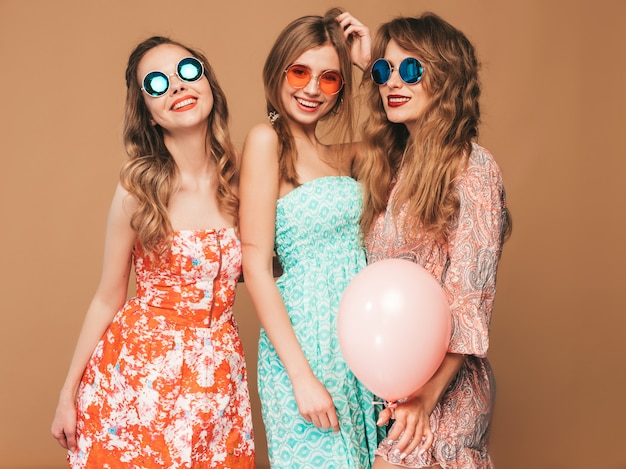 Drie glimlachende mooie vrouwen in de kleren van de geruite overhemdszomer. meisjes poseren. modellen met kleurrijke ballonnen in zonnebril. plezier hebben, klaar voor feest verjaardag of vakantie feest