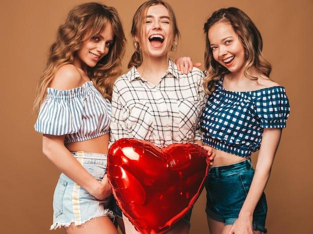 Drie glimlachende mooie vrouwen in de kleren van de geruite overhemdszomer. meisjes poseren. modellen met rode hartvormige ballon in zonnebril. klaar voor valentijnsdag van de viering
