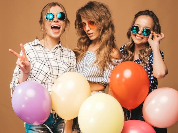 Drie glimlachende mooie vrouwen in de kleren van de geruite overhemdszomer. modellen met kleurrijke ballonnen in zonnebril. plezier, klaar voor de verjaardag van het feest