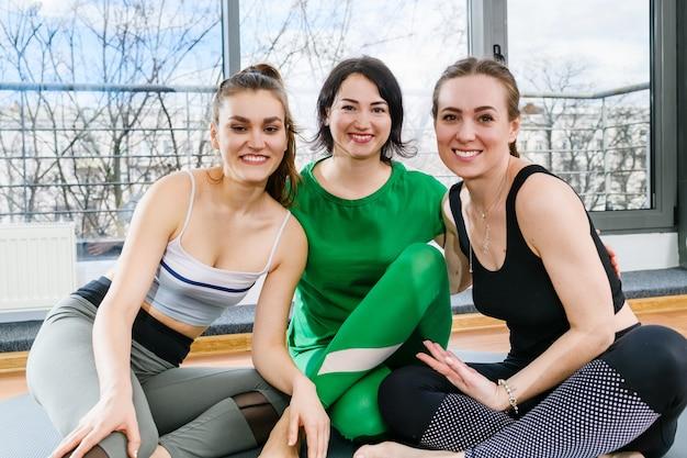 Drie glimlachende sportvrouwen die op blote voeten op matten zitten in lichte geschiktheidsstudio