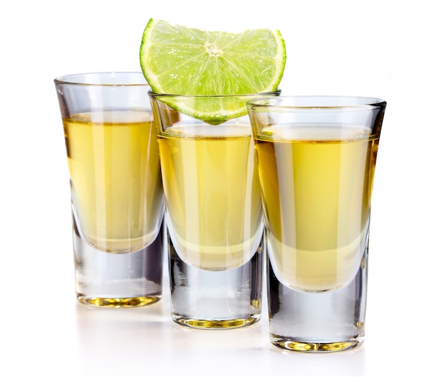 Drie gouden tequilaschoten met kalk die op wit wordt geïsoleerd