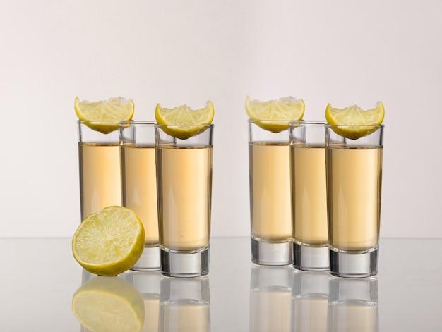 Drie gouden tequilaschoten met kalk op witte achtergrond