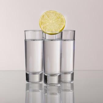 Drie gouden tequilaschoten met limoen geïsoleerd op een witte achtergrond