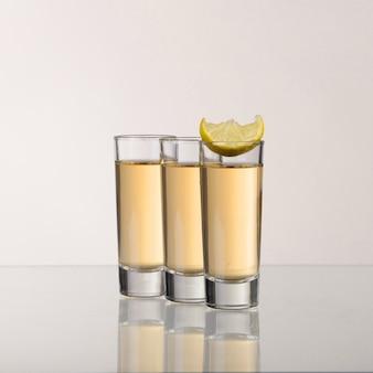 Drie gouden tequilaschoten met limoen op grijze achtergrond