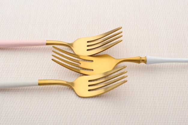 Drie gouden vorken op een roze tafelkleed. gouden bestekset