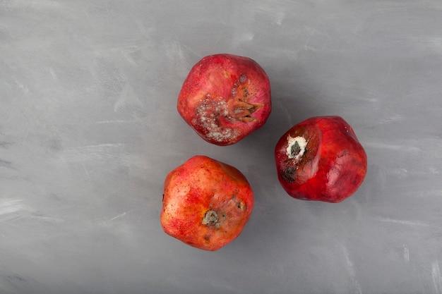 Drie granaatappels met schimmel