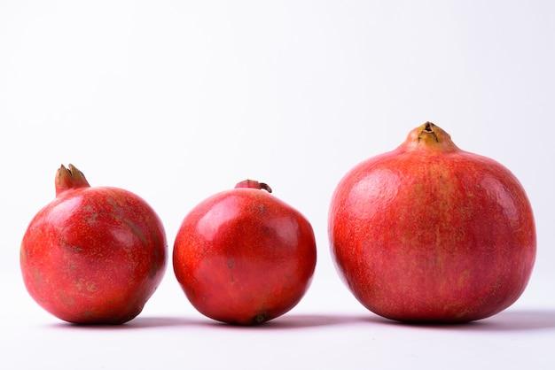 Drie granaatappels op een geïsoleerde rij