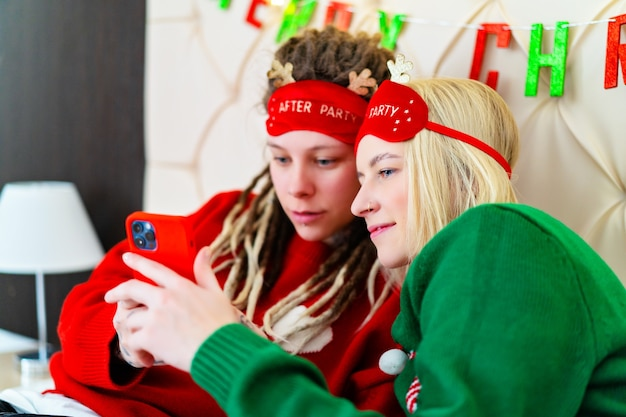 Drie grappige meisjes in kersttruien hebben online winkelen