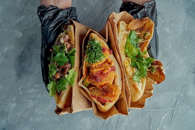 Drie griekse pitabroodjes worden in gehandschoende handen gehouden