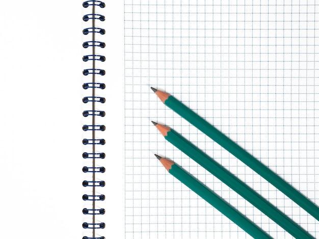 Drie groene potloden op wit notitieblok in de kooi met blauwe spiraaldraadbinding